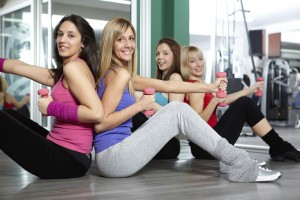 Four beautiful woman exercising in the gym with dumbbell